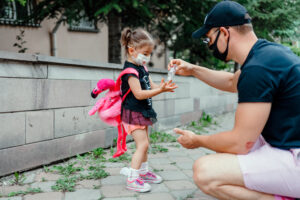little girl wearing a mask using hand sanitizer